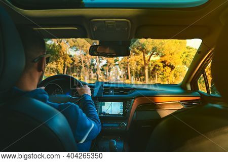 Young Man Driving Car At Summer Day On A Country Road At Sunset. Man Using Navigation System While D