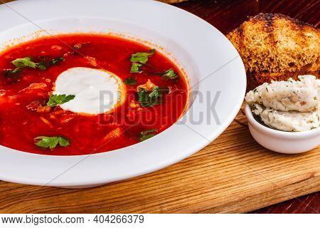 Traditional Ukrainian Russian Borscht Or Beetroot Red Soup With Sour Cream In White Plate