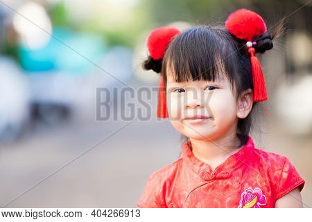 Asian Girl Dressed In Red Cheongsam And Decorated With Fluffy Hair Clips, With Red Tassels, To Celeb