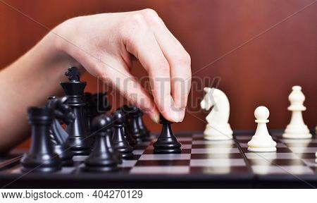 Closeup Of Boy Hand Holding Chess Figure While Playing Chess At Home. Education, Strategic Board Gam