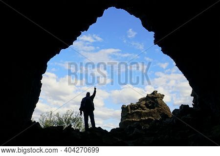 A Silhouette Of A Tourist Posed In Front Of The Old Church Rock Structure At Dimmuborgir Lava Format