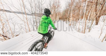 Fat bike winter sport biker cyclist biking girl riding on snow trail. Outdoor sport in nature forest background panoramic landscape.