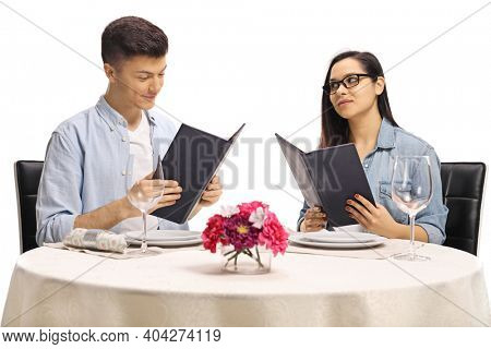 Jealous girlfriend looking at her boyfriend at a restaurant table isolated on white background
