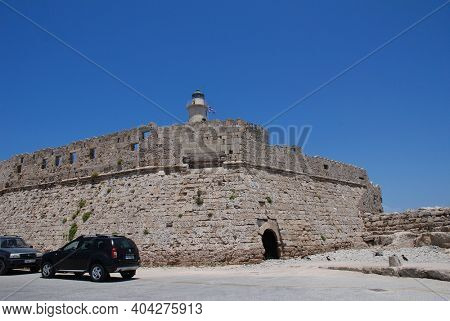 RHODES, GREECE - JUNE 9, 2019: The medieval Fort of Saint Nicholas by Mandraki harbour in the Old Town of Rhodes island. The fifteenth century fortification was built by the Knights of Saint John.