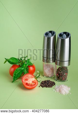 Electric Spice Mills. Nearby Salt, Pepper And Tomatoes. Green Background.electric Spice Mills. Nearb