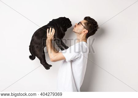 Profile Of Handsome Young Man Kissing Small Cute Dog Face. Hipster Guy Loving His Pug, Standing Over