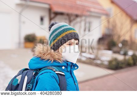 Kid Boy Wearing Ffp Medical Mask On The Way To School. Child Backpack Satchel. Schoolkid On Cold Aut