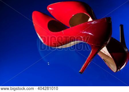 Beautiful Patent Leather Shiny Female Red Stilettos On A Blue Background