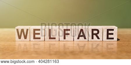 Welfare Word Written On Wooden Blocks On Wooden Table. Concept For Your Design.