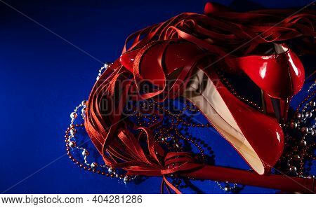 Beautiful Patent Leather Shiny Female Red Stilettos, Whip And Beads On A Blue Background