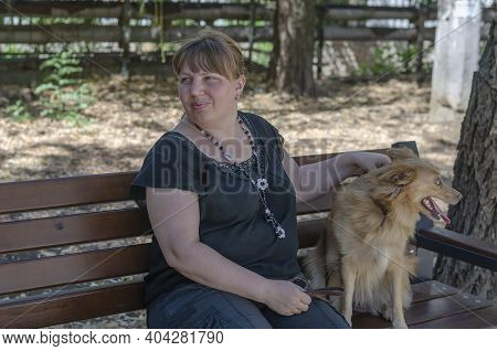 A Middle-aged Woman Sits On A Bench In A Summer Park With Her Dog. A 40-45 Year-old Woman And A Red