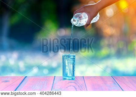 Drink Water Pouring In To Glass Over Sunlight And Natural Green Background.select Focus Blurred Back