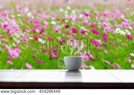 Hot Coffee Cup Of Love On Table Blurred Flower Background.valentine's Day Concept.