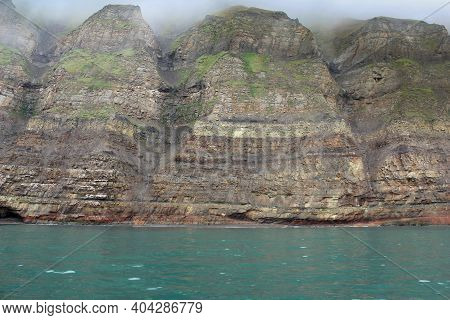 View From The Fjord To Steep And High Cliffs In The Fog. Typical Scandinavian Landscape. The Structu