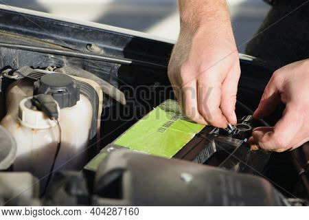 Hands Under The Hood Of The Car, Put The Car Battery. Repair, Maintenance. Hand Put Electric Pliers
