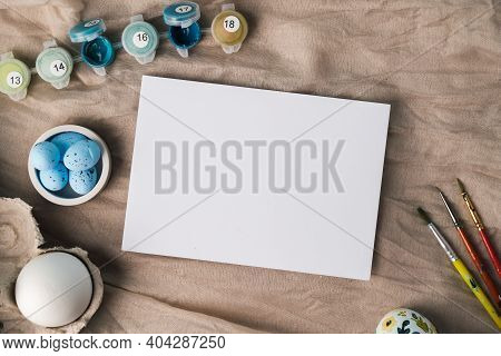 Mock Up For Easter Congratulations Or Ads. White Card Template And Easter Eggs With Acrylic Paint An