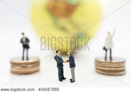 Miniature People: Businessman Handshake With Money And Globe, Investment, Agreement, Partnership And
