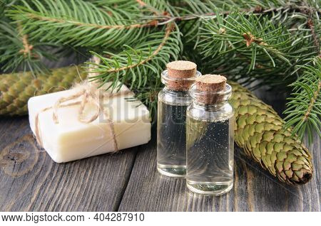 Two Bottles Of Spruce Essential Oil, Natural Soap And Fir Branches Behind.
