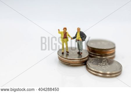 Miniature People: Elderly Person Standing On Coins Stack, Retirement Planning Concept.