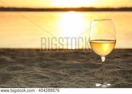 Glass Of Delicious Wine On Riverside At Sunset