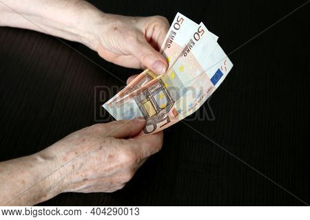 Elderly Woman With Euro Notes In Wrinkled Hands. Concept Of Pension Payments, Savings At Retirement,