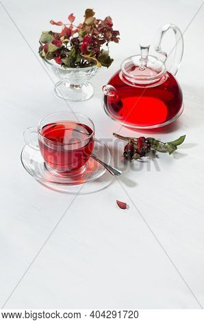Autumn Teatime With Red Herbal Tea In Transparent Tea Pot, Cup With Hawthorn Berries, Rose Hip, Dry