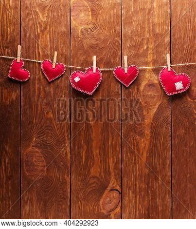 Concert For Valentine's Day. Red Hearts Made Of Felt Pinned With Clothespins To A String Against The