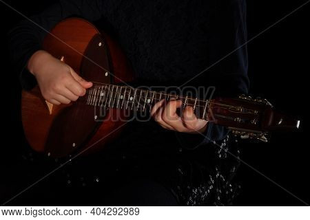 Childrens Hands Playing Domra Musical Instrument Isolated On Black Background