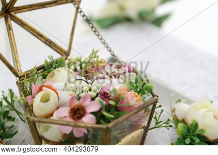Wedding Rings Of The Bride And Groom With Decorative Glass Box And Flower. The Wedding Ring Is Decor