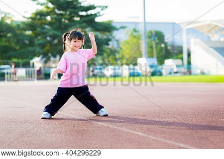 Adorable Asian Child Girl Is Exercising At The Sports Ground. Children Stands With Legs Apart And Ar