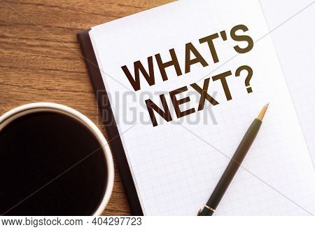 What's Next - Text On Notepad On Wooden Desk.