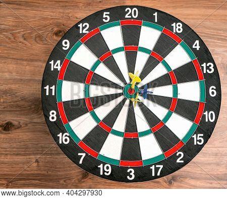 Flat Lay View Of A Dartboard With Three Darts In The Bull's Eye. Well-aimed Dart Throwing. Triple Bu
