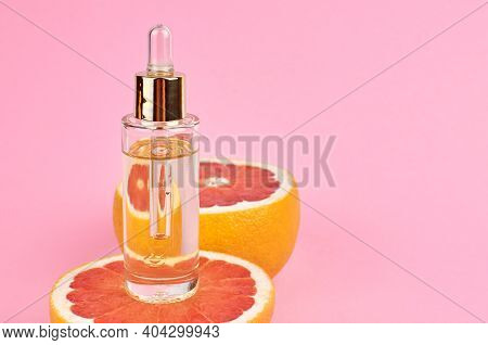 Grapefruit Pure Essential Oil With Fresh Grapefruit Halves On Pink Background