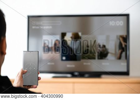 Man changing TV channel by his smartphone