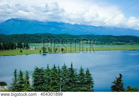 An Ancient Relict Lake In Pitsunda. Mountains Covered With Snow. Voluminous White Clouds Hang Over T