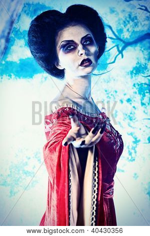 Portrait of a beautiful female vampire over moonlight background.
