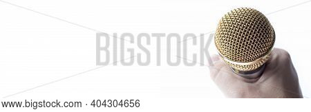 A Man's Hand Holds A Microphone On A White Background With A Gold-plated Tip. Space For Text,