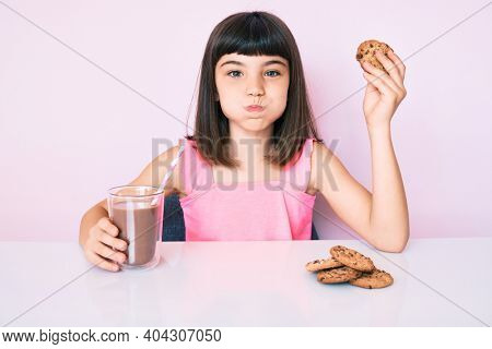 Young little girl with bang sitting on the table having breakfast puffing cheeks with funny face. mouth inflated with air, catching air.