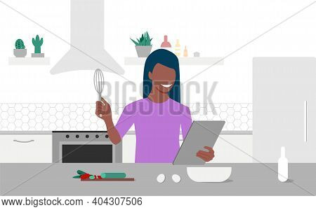 A Young Black Woman Looks On Tablet And Cooking By Online Video Tutorial In Her Kitchen. Online Culi