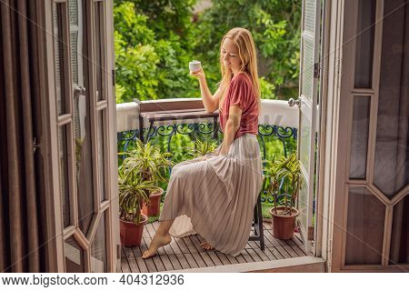 A Ginger-haired Woman Stands On A Heritage-style Balcony Enjoying Her Morning Coffee. A Woman In A H