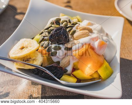 Close-up White Bowl With Bio Products: Yogurt, Mixture Of Cereals, Dried Fruit, Nuts, Healthy Seeds