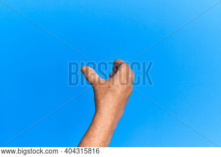 Hand of senior hispanic man over blue isolated background holding invisible object, empty hand doing clipping and grabbing gesture