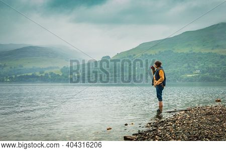 Mystical Foggy Lake In The Early Morning, Mountains On The Background.mature Woman Early In The Morn