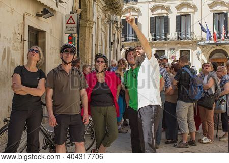 Lecce, Italy April 23, 2018 A Interested Group Of Tourists Look Up At A Historic Building. Guide To