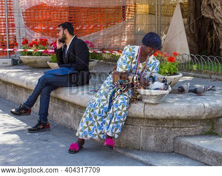 Lecce, Italy April 23, 2018 Black Women Selling Cheap Jewelry On The Street To Tourists. A Man Busin