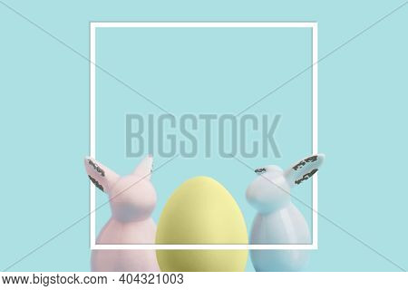 Easter Egg And Rabbits On Blue Pastel Background. Easter Greeting Card And White Frame With Space Fo