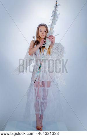 Cute Little Female Cupid Shoots A Bow. Innocent Girl. Cute Teen Girl. Cupid Cute Girl With A Bow. Va