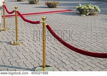 Golden Plated Barrier Posts With Red Velvet Ropes With Red Event Carpet