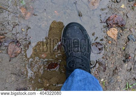 Water Splash From Shoes. Mens Feet In Hiking Shoes Steps Into A Puddle. Rain Footwear For Man Or Wom