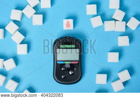 Diabetes Concept, Sugar Cube With Drawn Blood Drop, Sugar Cubes And Glucometer To Measure Blood Suga